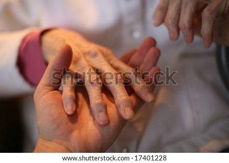 Young man 's hand holding senior's hand