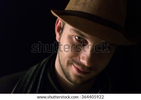 Young man's portrait in the dark. Close-up face. - stock photo