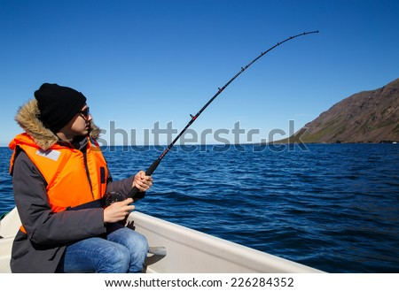 Young man salt water fishing, fish on the line - stock photo