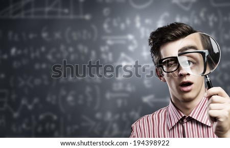 Young man scientist looking in magnifying glass - stock photo