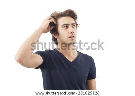 Young man scratching his head - stock photo