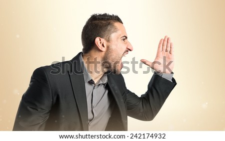 Young man screaming over isolated ocher background