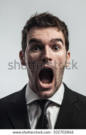 Young man screaming surprised looking at camera.