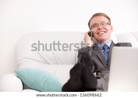 Young man seated on the sofa and speaking on the phone