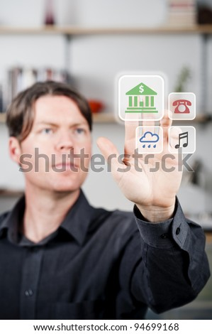 young man selecting a digital banking button - stock photo