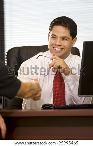 Young man shaking hands across his desk at work.