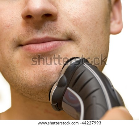 young man shaving his beard off with an electric shaver - stock photo