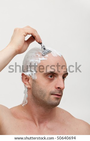 Young man shaving his head