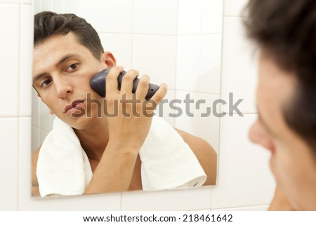 Young man shaving with electric shaver at the bathroom - stock photo