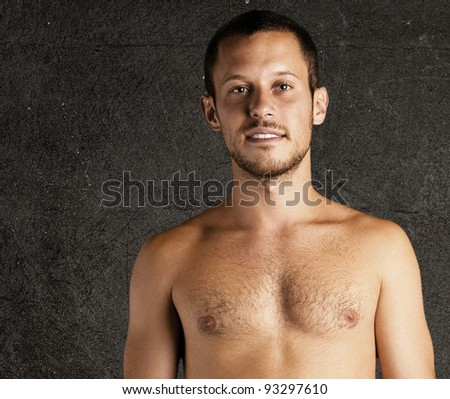 young man shirtless against a grunge background - stock photo