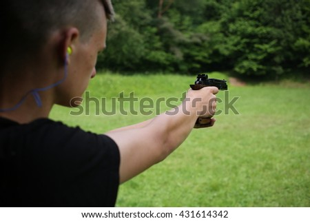 Young man shooting with hand guns - stock photo