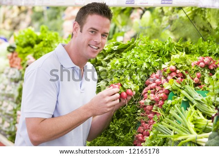 Young man shopping for fresh produce in supermarket - stock photo