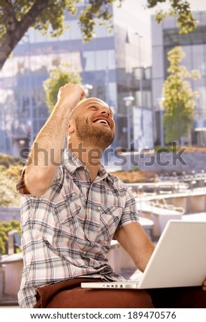 Young man shouting happy while sitting outdoors, using laptop computer, clenched fist. - stock photo