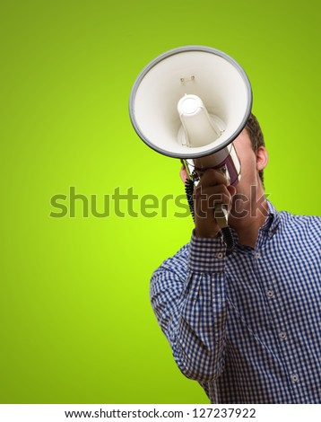 Young Man Shouting On Megaphone against a green background - stock photo
