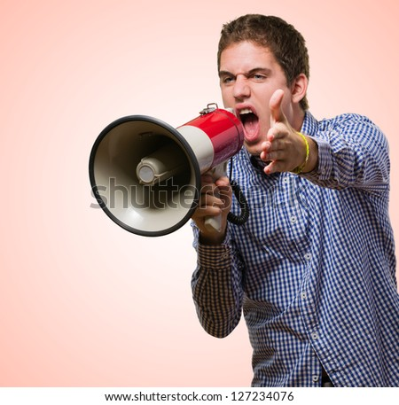 Young Man Shouting On Megaphone against a red background