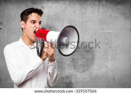 young man shouting with megaphone - stock photo