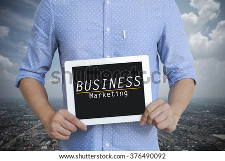 young man showing digital tablet with BUSINESS MARKETING on sky blackground , business concept ,business idea - stock photo