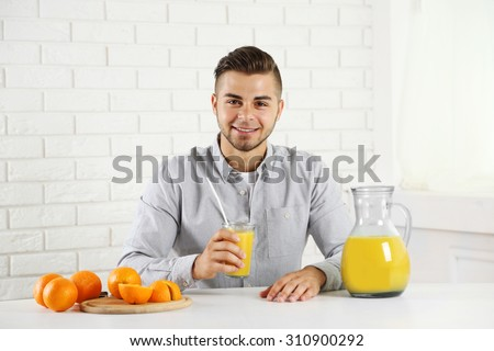 Young man showing glass of orange juice - stock photo