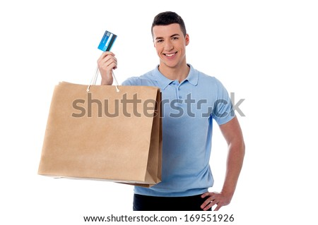 Young man showing his shopping bag and credit card - stock photo