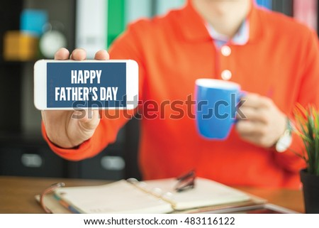 Young man showing smartphone and HAPPY FATHER'S DAY word concept on screen