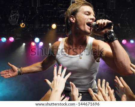 Young man singing on stage in concert with adoring fans reaching towards him - stock photo