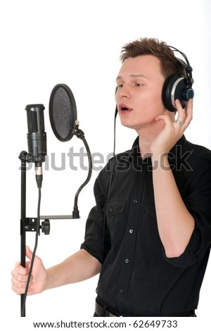 Young man singing song to microphone on white background