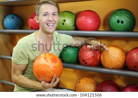 Young man sits near shelves with balls and holds orange ball in bowling club; shallow depth of field