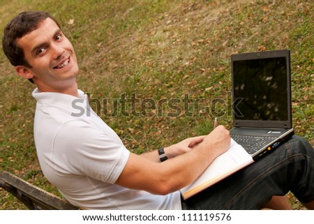 Young man sits on the bench with his laptop - stock photo