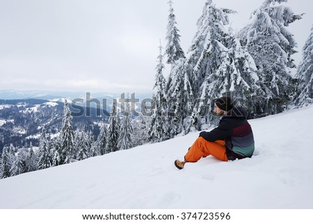 Young man sits on the mountain hillside and looks forward to the skyline view in front of beautiful pine trees in winter. Travel background with snow. Holidays in Carpathian mountains, Ukraine.