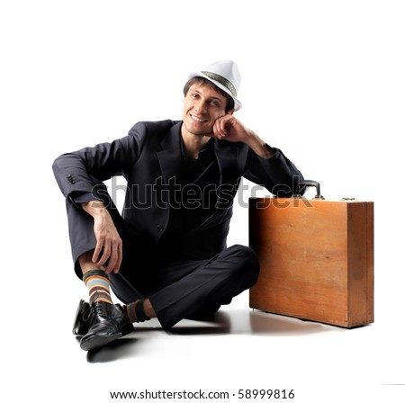 Young man sitting against a suitcase - stock photo