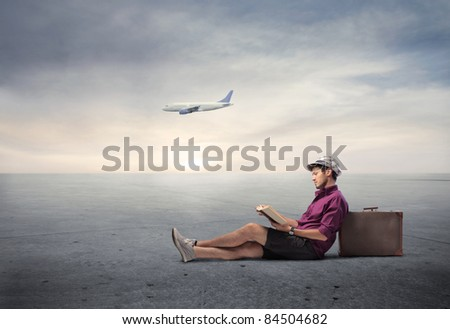 Young man sitting against a suitcase with airplane in the background