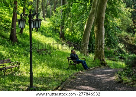 Young man sitting alone on a bench in a park. Concept for grief or sadness - stock photo
