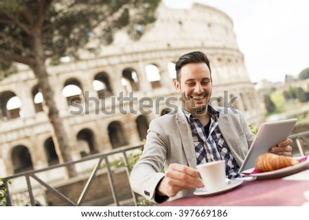 Young man sitting and having a cup of coffee in Rome, Italy - stock photo