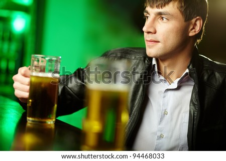 Young man sitting at bar counter with a pint of light beer - stock photo