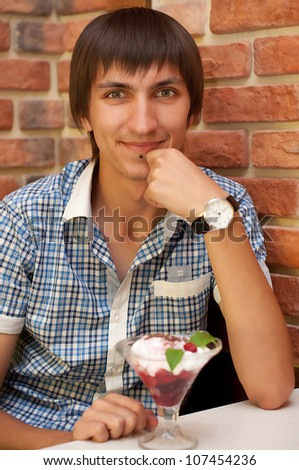 Young man sitting at cafe with cherry ice cream - stock photo