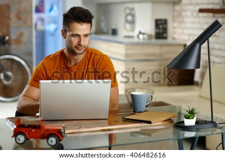 Young man sitting at desk at home, working on laptop computer.
