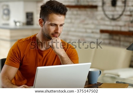 Young man sitting at desk, working with laptop computer, concentrating. - stock photo