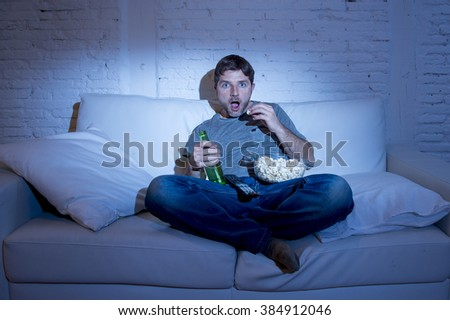 young man sitting at home sofa in living room watching movie or sport in tv eating popcorn and drinking beer in intense and concentrated face expression in television addiction - stock photo