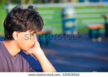 Young man sitting at park, deep in thought. Sad or unhappy - stock photo