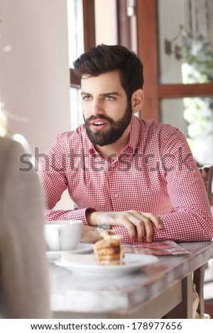 Young man sitting at table and chatting in coffee shop. - stock photo