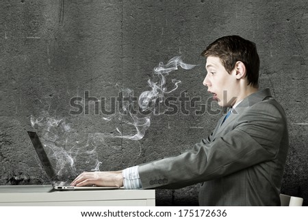 Young man sitting at table and using laptop - stock photo