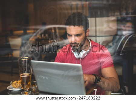 Young man sitting at the cafe and using laptop.Image taken from outside trough glass. - stock photo