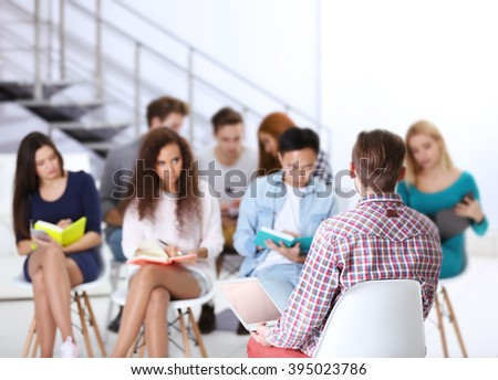 Young man sitting back in front of people at the office meeting - stock photo