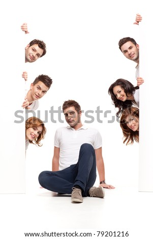 young man sitting between white boards with friends - stock photo