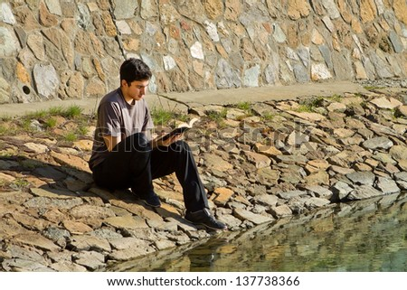 Young man sitting by a lake reading the Bible - stock photo