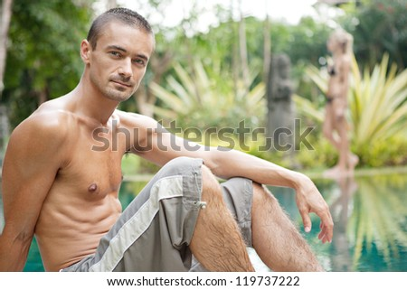 Young man sitting by a swimming pool in a tropical destination hotel spa with young woman walking passed in the background. - stock photo