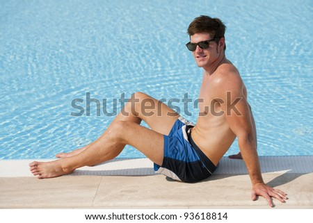 Young man sitting by swimming-pool - stock photo