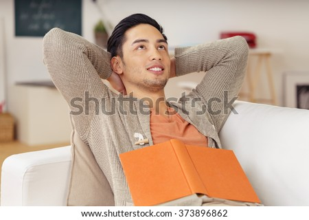 Young man sitting daydreaming at home on the sofa with a book resting on his stomach as he looks up into the air with a dreamy expression and smile - stock photo