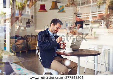 Young man sitting in a cafe eating a dessert - stock photo