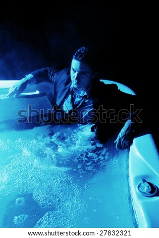 Young man sitting in a hot tub in a suit with his briefcase.